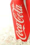 Coca - coladrink i en can på is som isoleras på vit bakgrund Arkivfoto