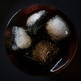 Coca with ice in a glass. On a black background Royalty Free Stock Photos