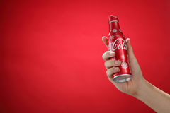 Cocacola. Kuala Lumpur,Malaysia 11th July 2016, Hand hold a bottle christmas edition of Coca-Cola on red background. Coca Cola drinks are produced and Royalty Free Stock Image