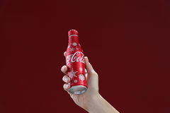 Cocacola. Kuala Lumpur,Malaysia 11th July 2016, Hand hold a bottle christmas edition of Coca-Cola on red background. Coca Cola drinks are produced and Stock Photo