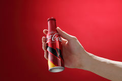 Cocacola. Kuala Lumpur,Malaysia 11th July 2016, Hand hold a bottle Coca-Cola limited edition of europe cup 2016 on red background. Coca Cola drinks are produced Stock Photos