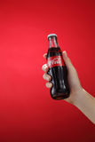 Cocacola. Kuala Lumpur,Malaysia 11th July 2016, Hand hold a bottle Coca-Cola on red background. Coca Cola drinks are produced and manufactured by The Coca-Cola Royalty Free Stock Photography