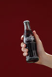Cocacola. Kuala Lumpur,Malaysia 11th July 2016, Hand hold a bottle Coca-Cola on red background. Coca Cola drinks are produced and manufactured by The Coca-Cola Royalty Free Stock Images