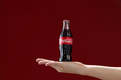 Cocacola. Kuala Lumpur,Malaysia 11th July 2016, Hand hold a bottle Coca-Cola on red background. Coca Cola drinks are produced and manufactured by The Coca-Cola Royalty Free Stock Photos