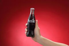 Cocacola. Kuala Lumpur,Malaysia 11th July 2016, Hand hold a bottle Coca-Cola on red background. Coca Cola drinks are produced and manufactured by The Coca-Cola Stock Photo