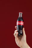 Cocacola. Kuala Lumpur,Malaysia 11th July 2016, Hand hold a bottle Coca-Cola on red  background. Coca Cola drinks are produced and manufactured by The Coca-Cola Stock Photography