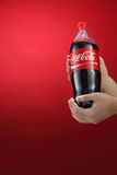 Cocacola. Kuala Lumpur,Malaysia 11th July 2016, Hand hold a bottle 1.5 litre Coca-Cola on red background. Coca Cola drinks are produced and manufactured by The Stock Photo