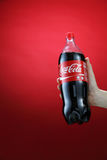 Cocacola. Kuala Lumpur,Malaysia 11th July 2016, Hand hold a bottle 1.5 litre Coca-Cola on red background. Coca Cola drinks are produced and manufactured by The Stock Images
