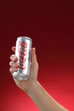 Cocacola. Kuala Lumpur,Malaysia 11th July 2016, Hand hold a can Coca-Cola light on red background. Coca Cola drinks are produced and manufactured by The Coca Stock Photography
