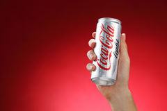 Cocacola. Kuala Lumpur,Malaysia 11th July 2016, Hand hold a can Coca-Cola light on red background. Coca Cola drinks are produced and manufactured by The Coca Stock Image