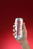 Cocacola. Kuala Lumpur,Malaysia 11th July 2016, Hand hold a can Coca-Cola light on red background. Coca Cola drinks are produced and manufactured by The Coca Stock Photos