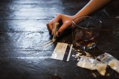 Cocaine alcohol addiction detrimental lifestyle. Cocaine and alcohol drink on dark background. Detrimental lifestyle. Bad habits. Alcohol and drug addiction Stock Photography