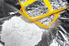 Cocaine dealing. Two bricks of cocaine wrapped in foil beside a heap of cocaine Stock Image
