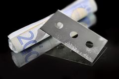 Cocaine gram bag and drug stained razor blade in addiction concept. Rolled money banknote for sniffing and snorting with cocaine stained razor blade on black Royalty Free Stock Image