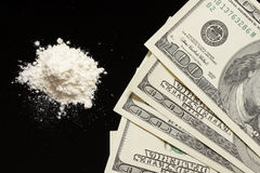 Cocaine and hundreds on black background Stock Photo