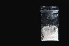 Cocaine in plastic packet on black background, closeup. Portion of drugs. Royalty Free Stock Photography