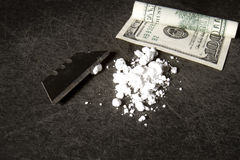 Cocaine. Powdered cocaine with razor blade and rolled up hundred dollar bill Stock Photo