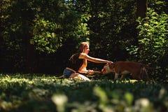 Coccole della ragazza di inginocchiamento il suo cane nel parco immagine stock libera da diritti