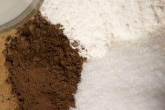 Cocendo con la farina dello zucchero del cacao Fotografia Stock