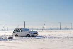 Coche abandonado del aceite cubierto por la nieve en fondo de los posts del invierno y de la electricidad Concepto del transporte Fotos de archivo libres de regalías