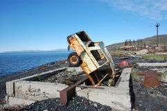 Coche abandonado oxidado roto viejo al revés en la costa de mar Foto de archivo libre de regalías