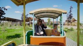 Coche abierto hermoso del paseo de la mujer y del niño pequeño en el parque zoológico del contacto almacen de metraje de vídeo