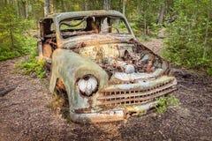 Coche aherrumbrado viejo del pedazo en un bosque foto de archivo