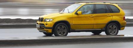 Coche alemán de lujo amarillo del suv x5, conduciendo rápidamente Imagen de archivo