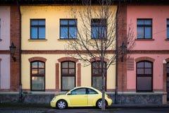 Coche amarillo contra la perspectiva de la casa colorida Imagen de archivo