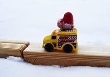 Coche amarillo del juguete que lleva el corazón hecho en casa del platicine Foto de archivo