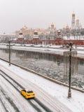 Coche amarillo del taxi delante de Moscú el Kremlin en el invierno foto de archivo