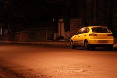 Coche amarillo en calle vacía de la noche Imagen de archivo