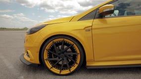 Coche amarillo-naranja en el estacionamiento, neum?ticos discretos de los deportes E r 05 almacen de metraje de vídeo