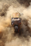 Coche amarillo que acciona para arriba la colina escarpada, golpeando para arriba la arena y el polvo con el pie Fotografía de archivo