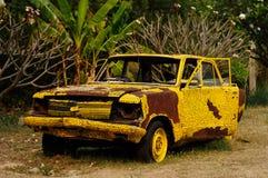 Coche amarillo viejo abandonado que aherrumbra en un campo Imagen de archivo libre de regalías
