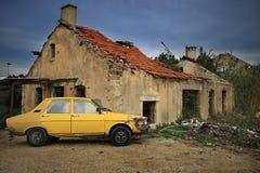 Coche amarillo y casa dilapidada Imagen de archivo