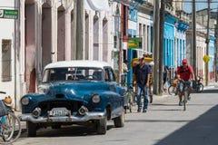 Coche americano azul del vintage en el chalet Clara de la provincia con la opinión de la vida en las calles foto de archivo