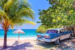 Coche americano del oldtimer del vintage en una playa en Cuba Foto de archivo