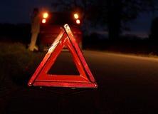 Coche analizado en la noche con la señal de peligro foto de archivo