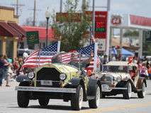 Coche antiguo con las banderas americanas en desfile en la pequeña ciudad América Imágenes de archivo libres de regalías