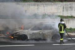 coche ardiente con los bomberos Fotografía de archivo