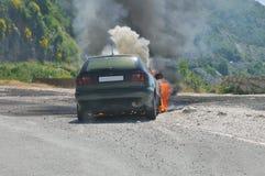 Coche ardiente en la carretera Imagenes de archivo