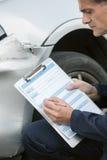 Coche auto de Inspecting Damage To del mecánico del taller y el completar R Fotografía de archivo