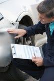 Coche auto de Inspecting Damage To del mecánico del taller y el completar R Imagenes de archivo