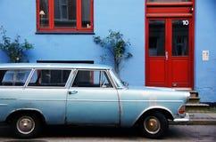 Coche azul al lado de la casa azul con la puerta y la ventana rojas Imagen de archivo
