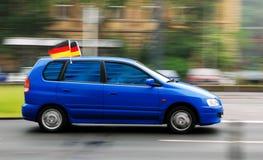 Coche azul con la bandera del aficionado al fútbol en el tejado Foto de archivo
