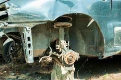 Coche azul dañado en accidente del desplome con la pintura rasguñada y la rueda delantera robada Foto de archivo