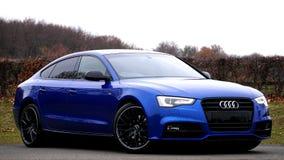 Coche azul de Audi en la calle Imagenes de archivo