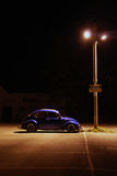 Coche azul estacionado bajo luz de calle Imágenes de archivo libres de regalías