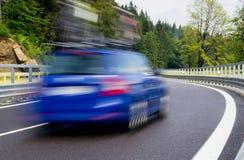 Coche azul rápido en un camino twisty Imágenes de archivo libres de regalías